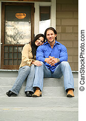 Happy With New House - two people sit in front of their new...