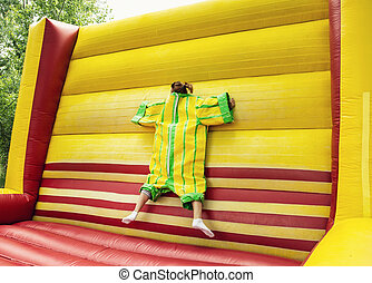 Young woman in plastic dress in a bouncy castle imitates a...