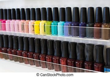 Set of different nail varnishes on shelves in cosmetic...