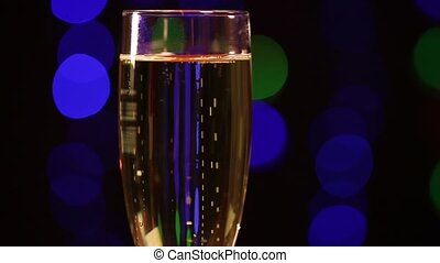 Glass with champagne in front of black background with...