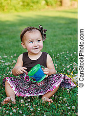 Happy Little girl playing in summer meadow on grass