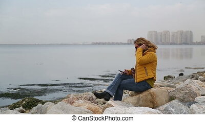 Woman sitting at the sea side - Woman sitting alone in rocks...