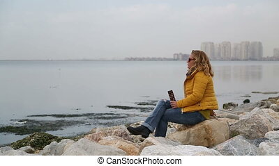 Woman sitting at the sea side and drinking coffee - Woman...