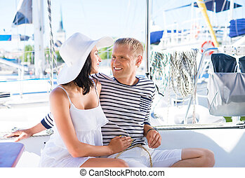 Young, rich and attractive couple on a sailing boat at...