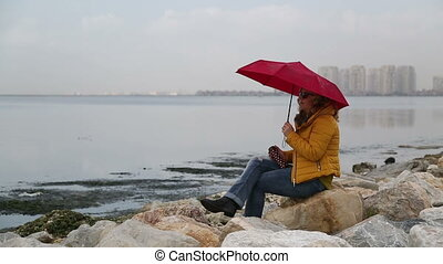 Woman sitting at the sea side - Woman with umbrella sitting...