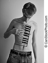 Piano Player - Young male playing a piano on his body. Black...