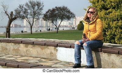 Woman sitting outdoor and drinking coffee - Smiling woman...