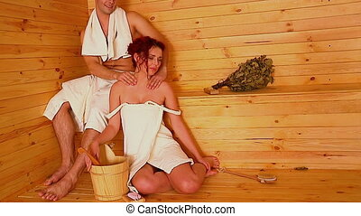 Couple are relaxing at sauna Man doing neck massage to girl...