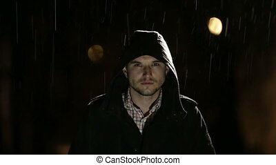 Handsome young man raise up his face to the rain in the dark...