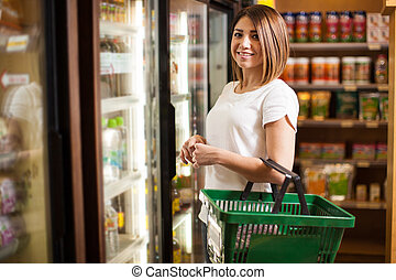 Cute Latin woman at a supermarket - Portrait of a pretty...