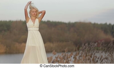 Attractive blonde woman in white dress standing outdoors in the green woods and her hair waving on the wind