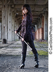 Dangerous asian girl with katana in ruins