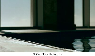 Silhouette of girl floating near the edge of the pool -...