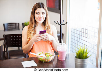 Gorgeous girl using a smartphone while having lunch -...