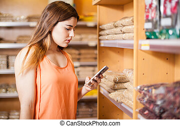 Woman using smartphone in a grocery store