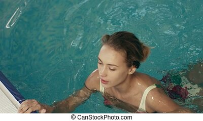Lovely girl swam over the edge of the pool - Lovely girl in...