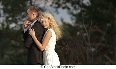 Young beautiful couple in the woods. She slowly comes to him, softly hugs and goes away. He continues standing brooding