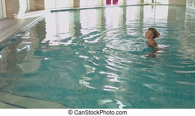 Blond girl swimming in the indoor pool - Well-groomed blond...