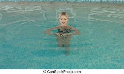 Beautiful girl swimming in the pool and swim to the edge of...
