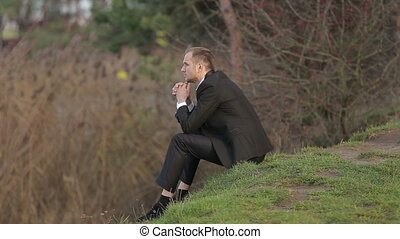 Close up of a young adult man lying on the hill with look of...
