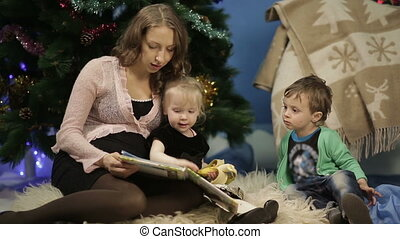 Mother with little children reading a book - Mother with her...