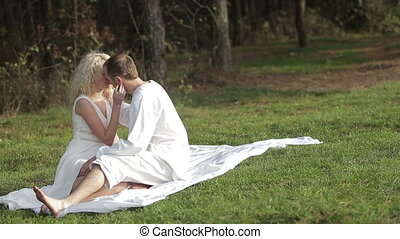 Young beautiful couple sitting on the green grass and...