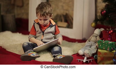 Boy with tablet PC near christmas tree - Child playing on...