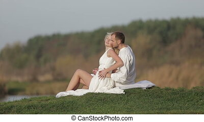 Young beautiful couple sitting on the green grass and kissing  in the woods