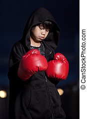 Young intense asian boy wearing boxing gloves
