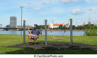 quot;man swinging on swing, watching riga view, latviaquot;...