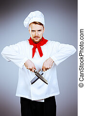 cooker - Portrait of a professional male cook holding knifes...