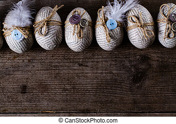 Easter eggs covered with scraps of newspaper wrapped in a...