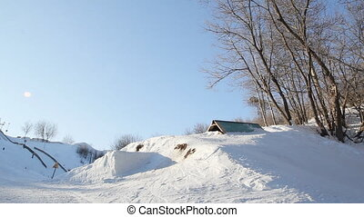 Male snowboarder slides from the mountain in winter day.
