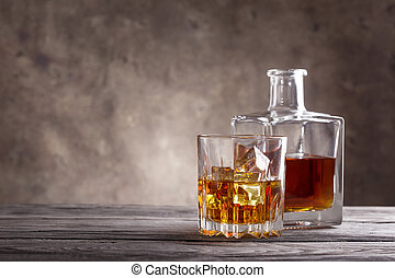 Square decanter and glass of whiskey on wooden table
