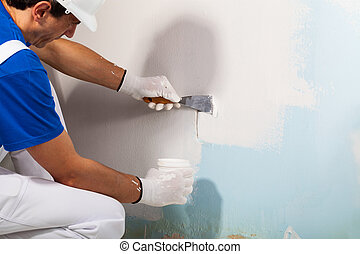 Workman Applying Plaster with Putty Knife - Close-up Of...