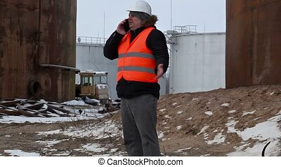 Engineer talking on the smartphone in the factory near to...