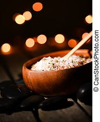 Pink sea salt with herbs in bowl with backlights