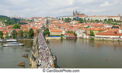 """prague castle view, people walking crossing charles bridge, czech republic"""