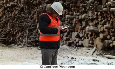Engineer take picture near to piles of logs in winter