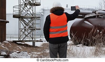 Engineer filming near to the oil tanks