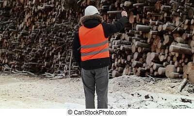 Engineer filming near to piles of logs in winter