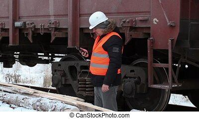 Railway officer take picture near freight wagons