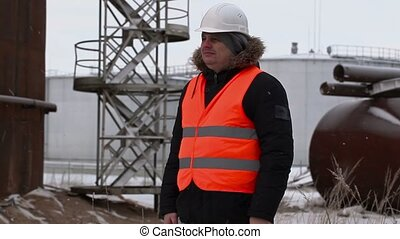 Engineer near to the oil tanks