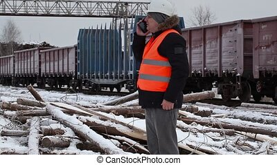 Railway officer talking on the smartphone near freight...