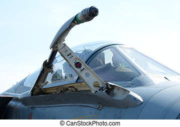 Retractable refueling probe on military fighter jet.