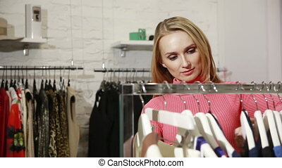 Young woman choosing clothes on a rack in a showroom - Young...