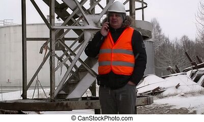 Engineer near to the oil tank in winter
