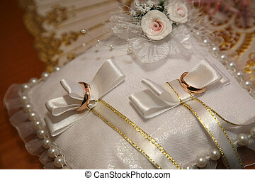 gold wedding rings lie on a decorative pillow