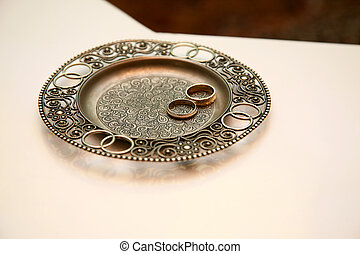 gold wedding rings lie on a metal plate