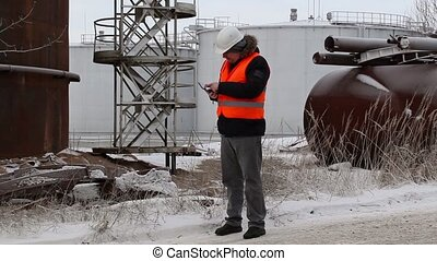 Engineer using tablet PC near to the oil tanks